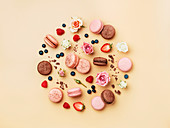 Round composition with french macarons, flowers and berries on cream yellow background