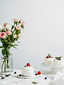 Mini Pavlova cakes with fresh berries and rosemary on white marble tabletop with flowers in glass vase bottle and white wall background