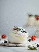 Icing sugar sprinkles on mini Pavlova cake with fresh berries and fresh green rosemary. Vertical composition with white marble tabletop and white wall background. Copy space top.