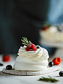 Mini Pavlova cake with fresh berries and fresh green rosemary. Vertical composition close-up with white marble tabletop and dark background of apron. Copy space top.