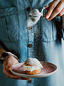 Woman in blue denim shirt holds with one hand pink plate with choux au craquelin pastry and sprinkles with her other hand icing sugar through a sieve s. Vertical composition.