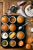 Homemade citrus oranges or clementines sweet muffins cakes in baked tray with flour, ingredients and different topping