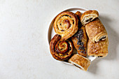 Variety of traditional french puff pastry buns with rasin and chocolate, croissant over white texture background
