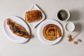 Variety of traditional french puff pastry buns with rasin and chocolate, croissant with paper cup of coffee and milk