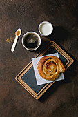 Traditional french puff pastry buns with rasin and custard on slate wooden board with paper cup of coffee and milk