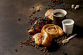 Variety of traditional french puff pastry raisin and chocolate buns, croissant with cups of coffee americano and milk