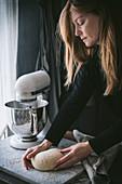 Frau knetet Brotteig auf Marmorarbeitsplatte