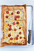 Tomato zucchini tart on a baking sheet