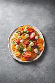Italienischer Caprese-Salat mit roten und gelben Tomaten, Mozzarella und Basilikum