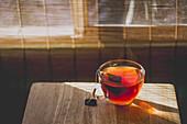 Eine Glastasse Tee auf Tisch im Sonnenlicht