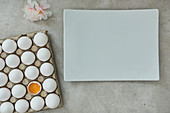 Egg carton with a cracked egg, a porcelain plate and a flower on a gray background