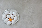 White eggs and a cracked egg on a ceramic plate