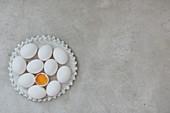 Weisse Eier und aufgeschlagenes Ei auf Keramikteller