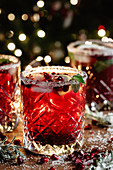 Pomegranate cocktail with mint and Christmas lights on the background
