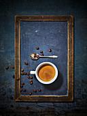 Ein Tasse Espresso mit Kaffeebohnen und Löffel