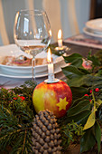 Apple with star motif used as candle holder on set table