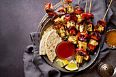Grilled onion and pepper paneer skewers with, flatbread and chili sauce