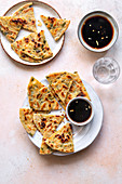 Chinese scallion pancakes on the plate served with chilli soy sauce