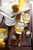 Limoncello with ice cubes and fresh lemon peel