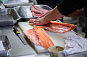 Fish being filleted in a commercial kitchen