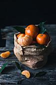 Clementinen in Papiertüte, eine geschält