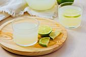 Homemade refreshing lemonade in server in glasses on wooden tray in white table background