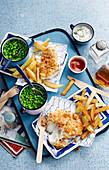 Fish & Chips mit Erbsen, Saucen und Essig