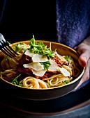 Mann hält Spaghetti mit Austernpilz-Tomaten-Sauce
