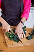 Frau schneidet frischen Grünkohl