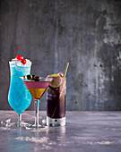 Drei Cocktails: Blue Lagoon, Purple Rain und Aviation