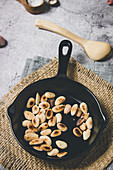 Roasted almond nuts on black metal pan on burlap napkin in composition with wooden spoon