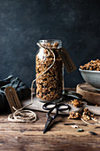 Glass jar of fresh millet and quinoa granola with label placed on wooden table