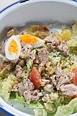 Closeup yummy tuna salad with potatoes and tomatoes mixed with egg and lettuce