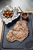 Piece of tasty grilled meat placed on tray near sauce on table