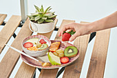 Hands having healthy breakfast and eating delicious yogurt with sliced fresh assorted fruits served on wooden table