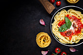 Tagliatelle pasta served in pan with tomato sauce and fresh basil leaves on black background