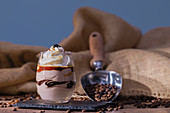 Cup with tasty parfait placed near scoop with roasted coffee beans against rough linen cloth
