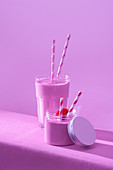 Yummy milkshake with fresh ripe strawberry on table in pink light