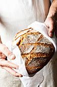 Baker holds freshly baked bread