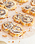 Poppy seed puff pastry buns with icing and flaked almonds