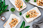 Cassava fries with wild garlic salsa verde in bamboo bowls
