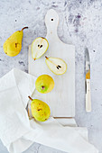 Small pears on white cutting board