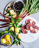 Lebensmittelstilleben mit Kalbshaxen, Rhabarber, Zitronen und Brombeeren