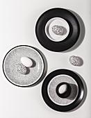 Schwarz-weiße Ostereier auf schwarzen, weißen und gesprenkelten Tellern