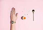 A woman's arm with a wristwatch next to a open hard-boiled egg and an egg spoon