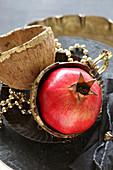 Granatapfel in vergoldeten Kokosnussschalen als Deko