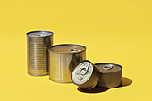 Various tins on a yellow surface