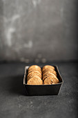 Spelt cookies with almonds in a box against a gray background