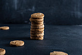 A stack of spelt cookies with almonds against a dark background