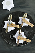 Place cards made from DIY origami stars and antique spoons with stamped mottoes on labels